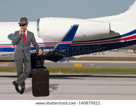 Business man standing next to a private jet - stock photo