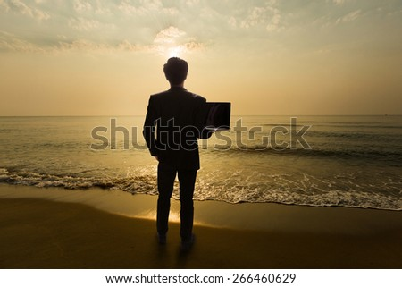 Business Man Standing on the beach in the morning. Are using a notebook computer.