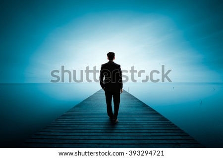 Business man standing on wooden bridge and looks at the sea, Business concept