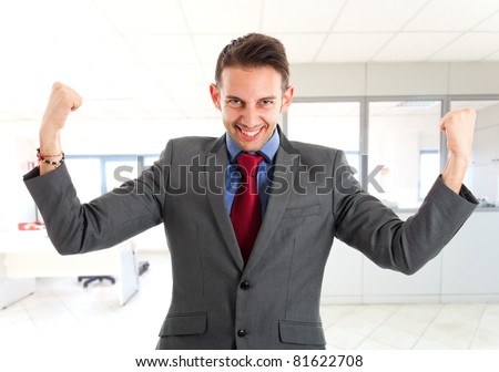 Business man standing with fists clenched in sign of victory - stock photo