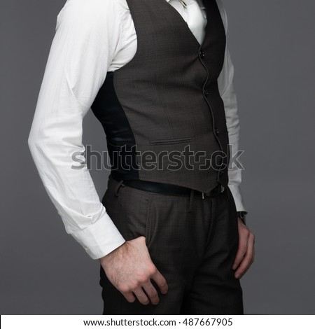 Business man standing with hands in his pockets, on a grey background, stock picture