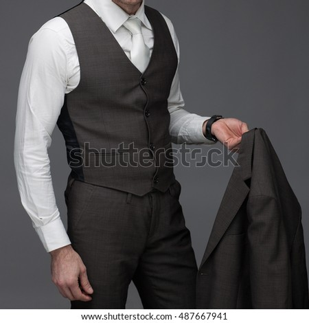 Business man standing with jacket in his hand, on a grey background, stock picture