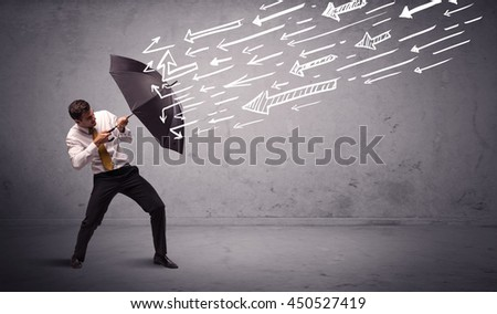 Business man standing with umbrella and drawn arrows hitting him on grungy background - stock photo