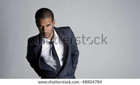 Business man stands in studio showing off his suit