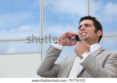 Business man stood outdoors using mobile telephone - stock photo