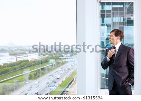 Business man straightens his tie at the window in the office - stock photo