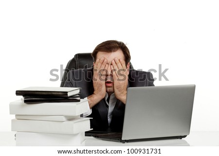 Business man stressed out in his office with a lap top and a lot of papers in front of him holding his head and eyes - stock photo