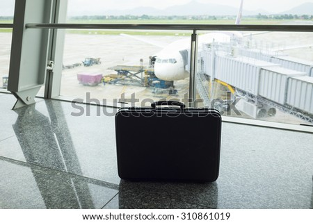 Business man suitcase against air plane on background at airport. Concept of business man travelling by airway - stock photo