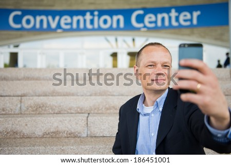 Business man taking a selfie with his smart phone in front of a convention center - stock photo