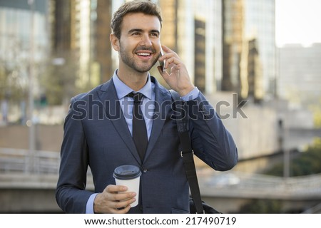 Business man talking on a cell phone smiling downtown - stock photo