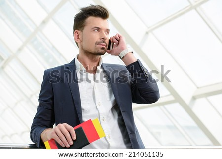 Business man talking on phone traveling walking inside in airport. Casual young businessman wearing suit jacket and shoulder bag. - stock photo