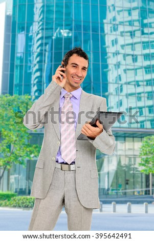 Business man talking on the phone and holding a tablet outdoors over city background