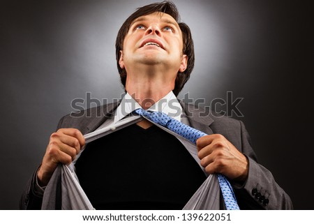 Business man tearing off his shirt over gray background - stock photo