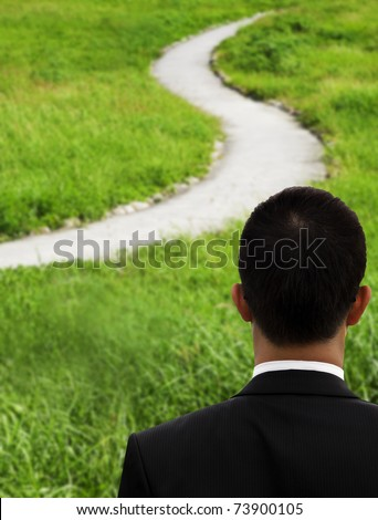 Business man thinking and watching the curved road - stock photo
