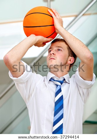 Business man throwing a basketball indoors - stock photo