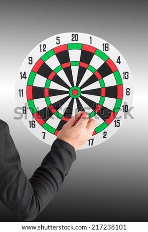 business man throwing darts at dart board classic - stock photo