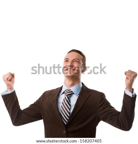 Business man throwing fists in air and smiling while celebrating success isolated on white background