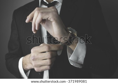 business man tied the hands of the watch - stock photo