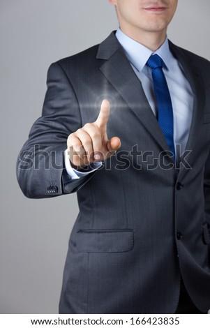 Business man touching an imaginary screen - stock photo