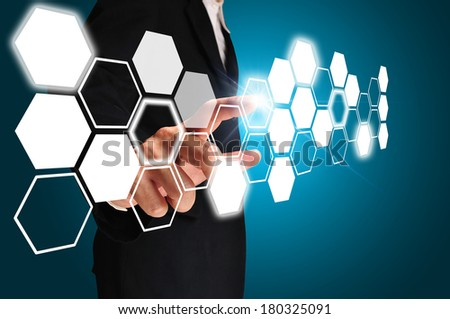 Business man touching an imaginary screen on blue background - stock photo
