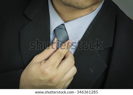 business man touching his tie. Close up,Closeup portrait of businessman in blue collar shirt and suit with tie. - stock photo