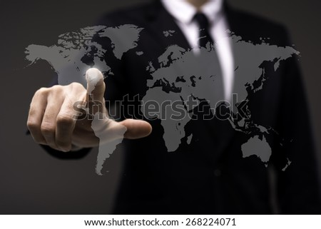 Business man touching imaginary screen with world map - stock photo
