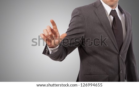 business man touching virtual screen, grey background