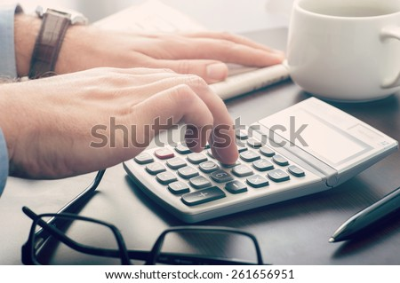 Business man using a calculator at his desk - stock photo
