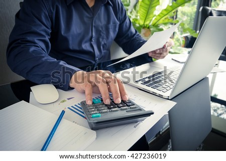 business man using a calculator to calculate the numbers - stock photo