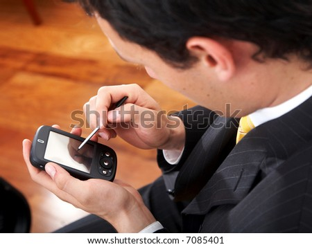 business man using a pda in his office - stock photo