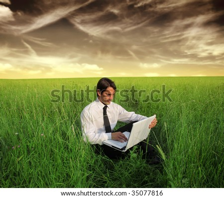 business man using laptop in a grass field - stock photo