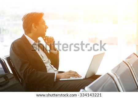 Business man using laptop while waiting his flight at airport, beautiful golden sunset background. - stock photo