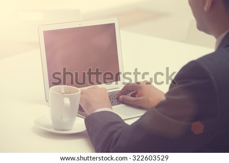business man using laptop with coffee in the morning - stock photo