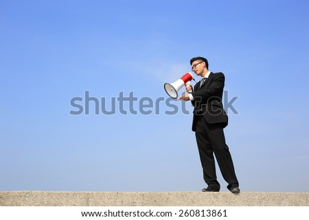 business man using megaphone shouting with blue sky background, asian - stock photo