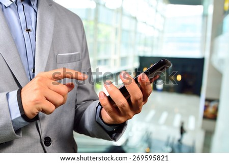 Business Man using Mobile Cell Phone in The Modern office building. - stock photo