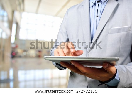 Business Man Using Mobile Digital Tablet in Modern Building.  Selective Focus on Tablet - stock photo