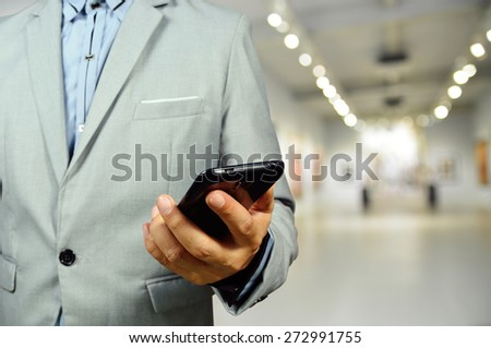 Business Man using Mobile Phone in the Art Gallery Hall as Wireless Technology concept. Selective Focus on Hand and Phone. - stock photo