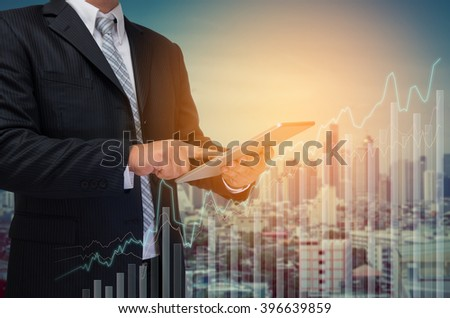 business man using tablet monitor graph on screen with city background - stock photo