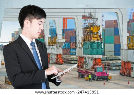 Business man using tablet to handle export and import Container transport - stock photo