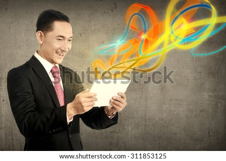 Business man using tablet with ray of light out from device