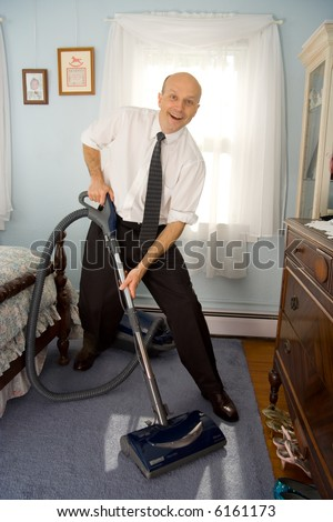 Business man vacuuming bedroom carpet