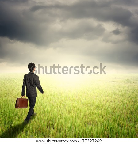 Business man walking and holding bag in fields and rainclouds