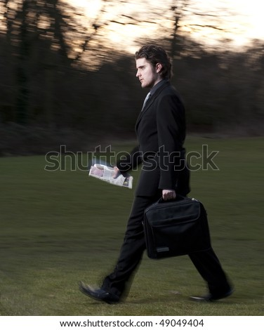 Business man walking briskly, carrying a brief/laptop case and a newspaper. - stock photo