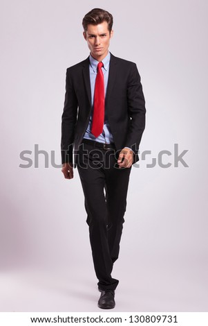 business man walking towards the camera and looking forward with a serious look, on gray - stock photo