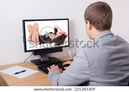 business man watching erotic video on his personal computer in office