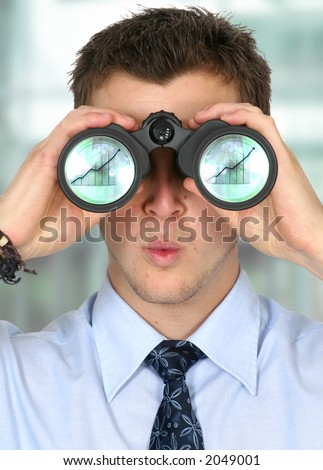 business man watching his business finances grow - there are column graphs on the reflections of the lenses - stock photo