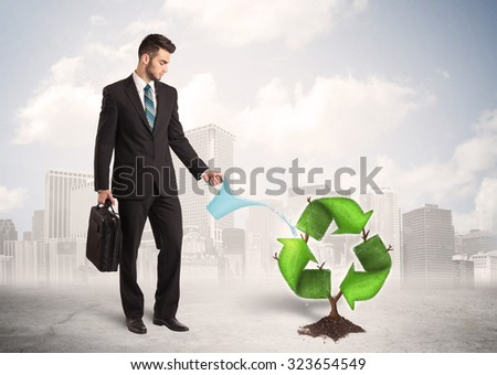 Business man watering green recycle sign tree on city background concept