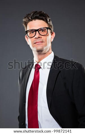 Business man wearing retro glasses with blue suit and red tie isolated on dark background. Studio shot.