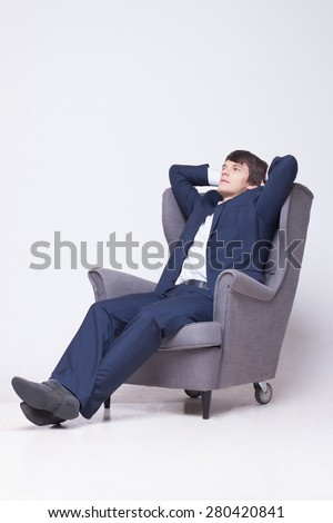 business man wearing suit  on  chair over white background