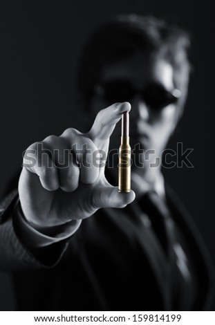 Business man wearing sunglasses holding a bullet